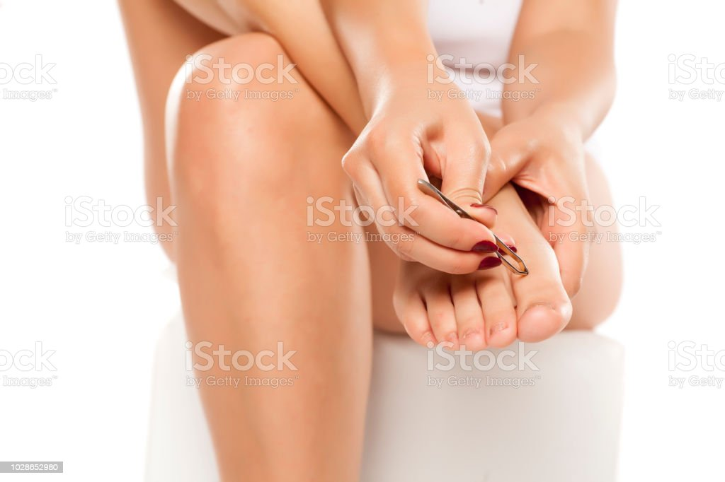 young woman pulls out the hairs on her toes with tweezers on white background stock photo