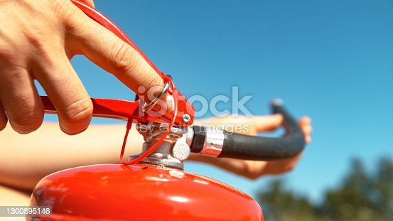 MACRO, DOF: Young woman pulls safety pin out of a fire extinguisher before using it in an outdoor fire drill. Unrecognizable girl pulls out the safeguard before using a portable fire extinguisher.