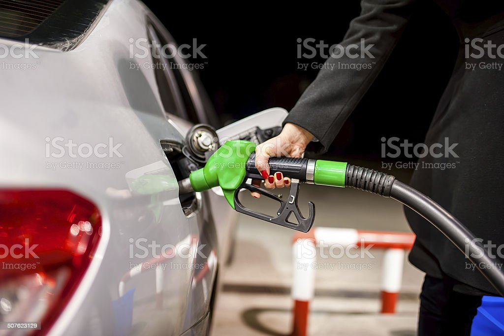 Young woman pumping gas in car at petrol station stock photo