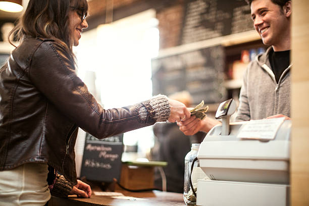 Young woman purchasing coffee A woman is paying at a coffee shop.  The cashier is a young man.  They are smiling at each other. paper currency stock pictures, royalty-free photos & images