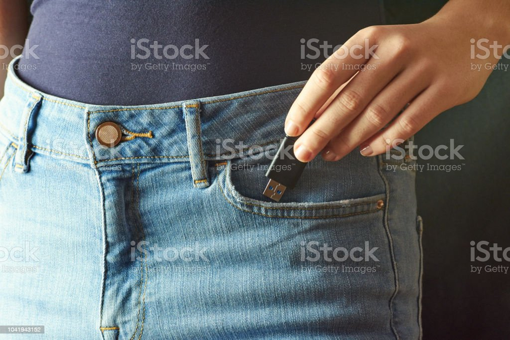 Young woman pushing a flash disk into a jeans pocket. Holds Flash Drive in hand. Dark background. stock photo