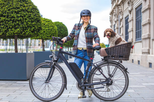 young woman pushing her e-bike with the dog in the basket stock photo