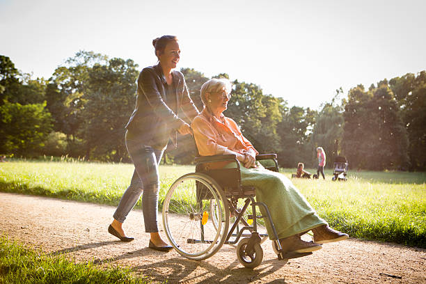 young woman pushing senior lady in wheelchair through a park stock photo