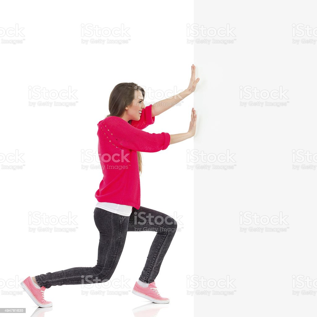 Young woman pushing the wall stock photo