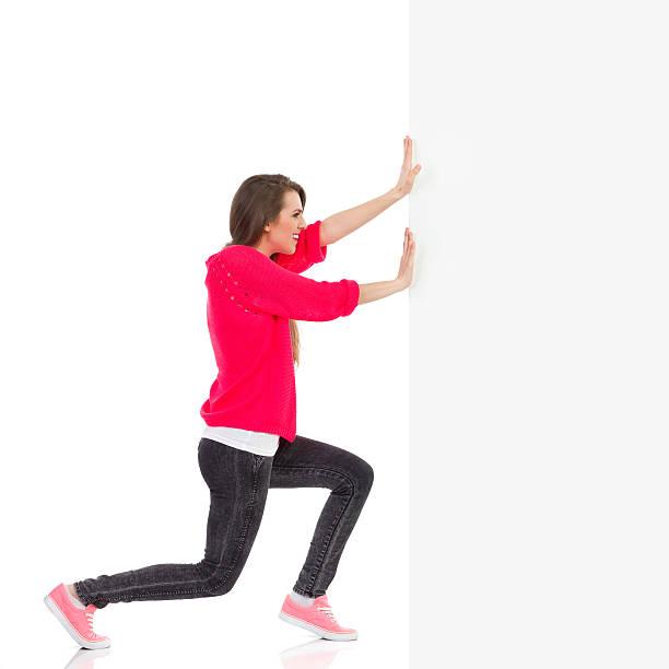 若い女性の壁押し - 押す ストックフォトと画像