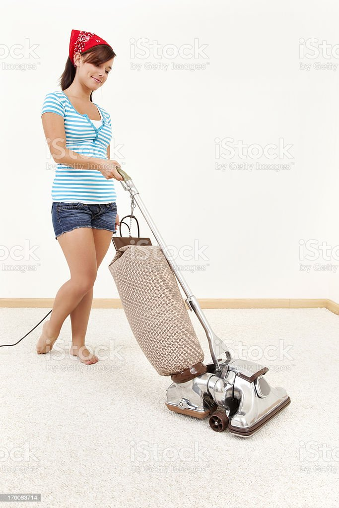Young Woman Pushing Vacuum Cleaner royalty-free stock photo