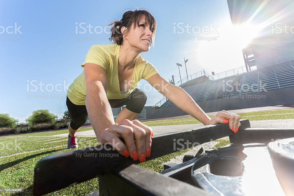 Young Woman Pushing Weighted Sled royalty-free stock photo