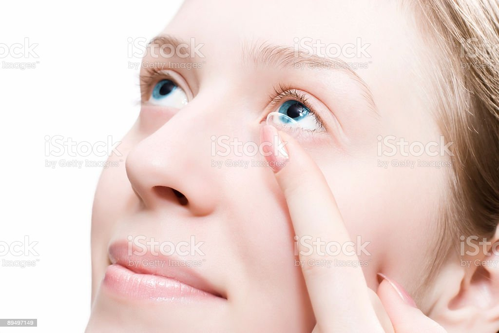 Young woman puting a contact lens royalty free stockfoto