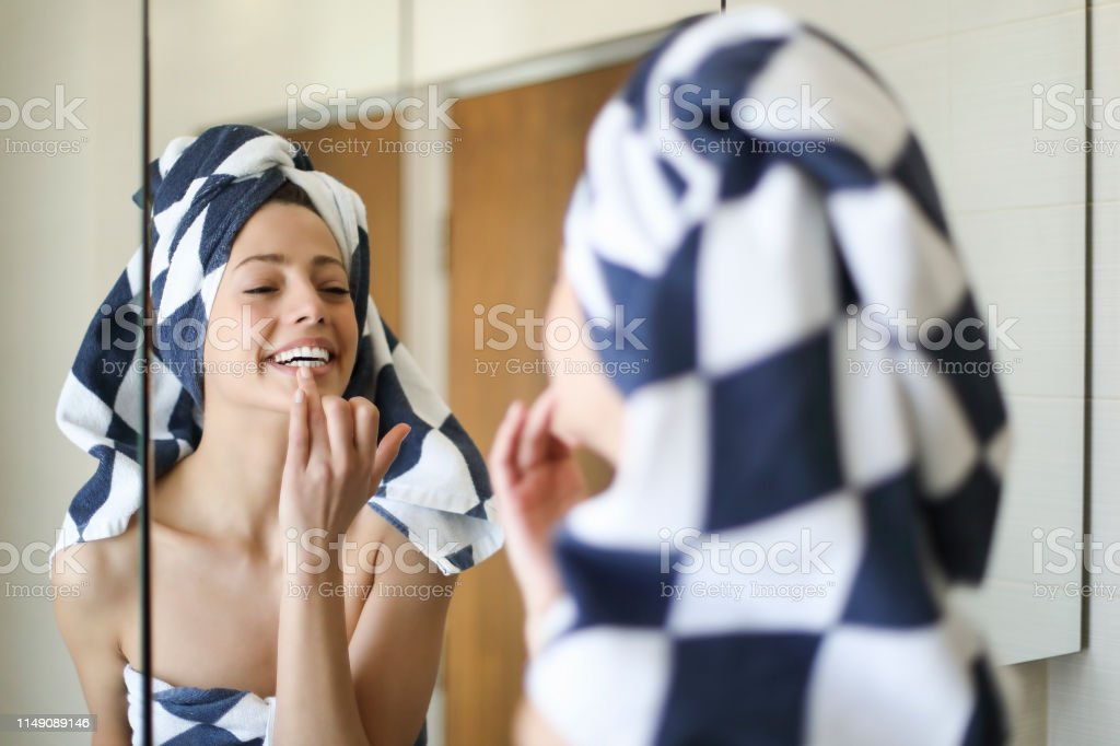 Young woman puting make up on - Foto stock royalty-free di Accudire