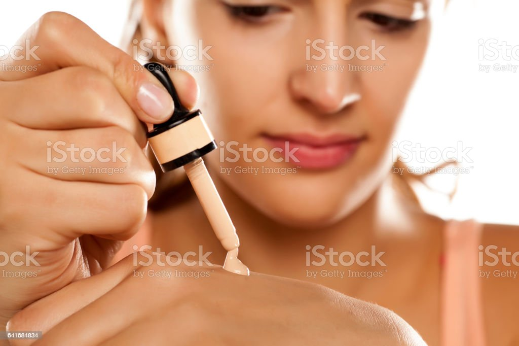 young woman puts a liquid foundation on her palm stock photo