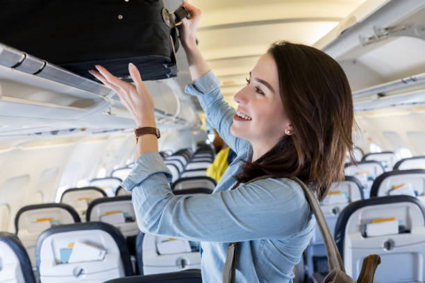 Young woman puts carry on bag in overhead bin of airliner A cheerful young woman stands in the aisle of a commercial airliner and pushes her suitcase into an overhead bin. carry on luggage stock pictures, royalty-free photos & images