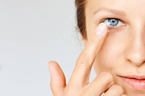 Young woman puts contact lens in her eye. stock photo
