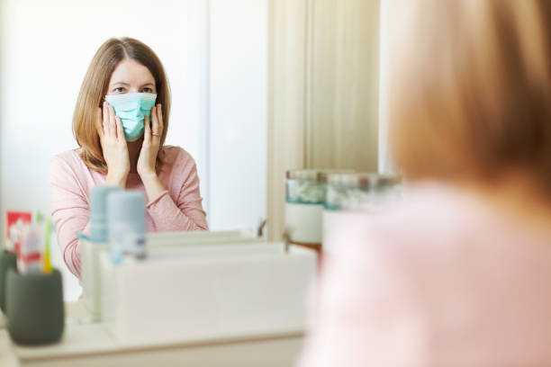 een jonge vrouw zet op een op masker voor de badkamersspiegel - mirror mask stockfoto's en -beelden