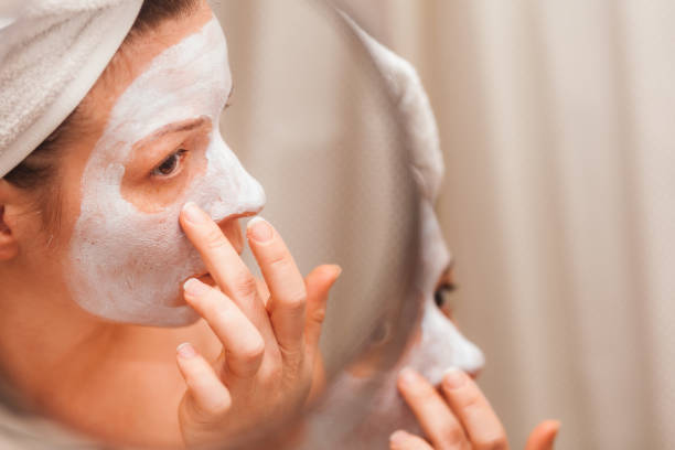 Young woman putting a cream on her face stock photo