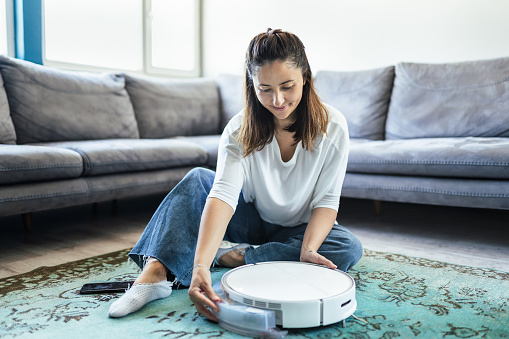 Young Woman putting a mop part to robotic vacuum cleaner