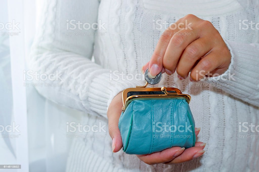 Young woman putting coin in purse. Leather purse for coins. - foto de acervo