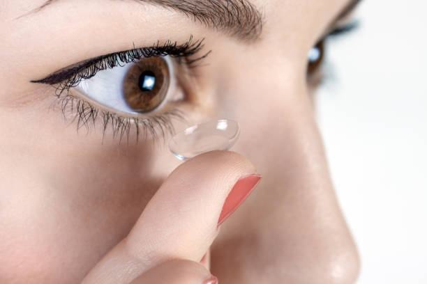 Young woman putting contact lens in her right eye, close up stock photo
