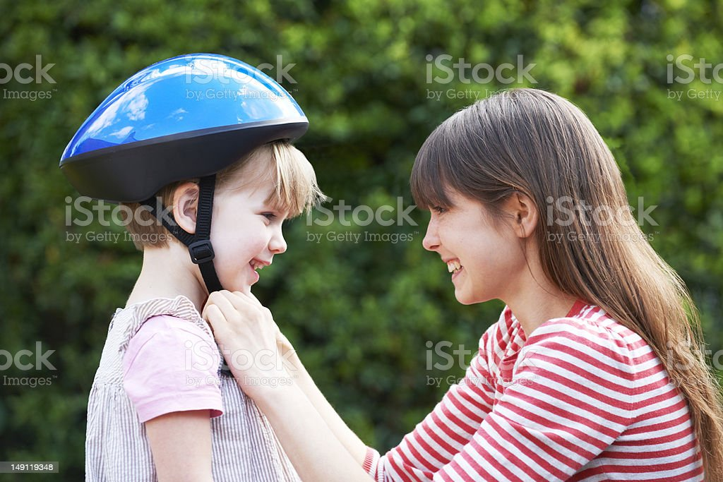 Young Woman Putting Cycle Helmet Onto Girl stock photo