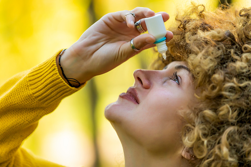 Woman Uses Eye Drops for Eye Treatment. Closeup of eyedropper putting liquid into open eye