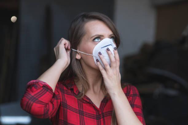 Mujer joven poniendo máscara facial para el aire contaminado - foto de stock