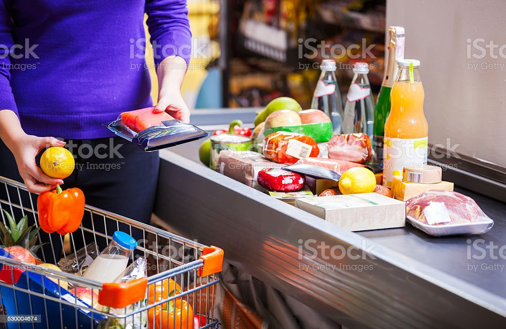 Young woman putting goods on counter in supermarket stock photo