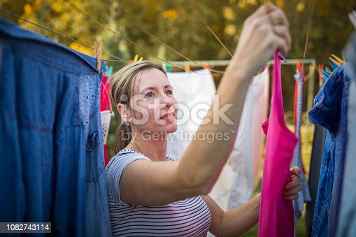 Young woman putting laundry on a rope in her garden,  taking great care of her family on a daily basis