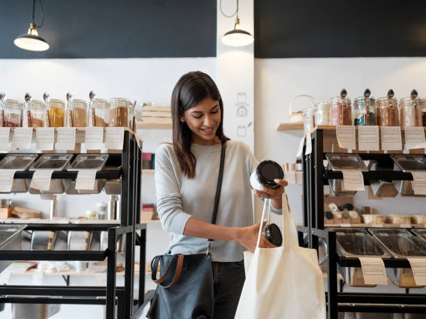 Young woman putting merchandise in reusable shopping bag stock photo