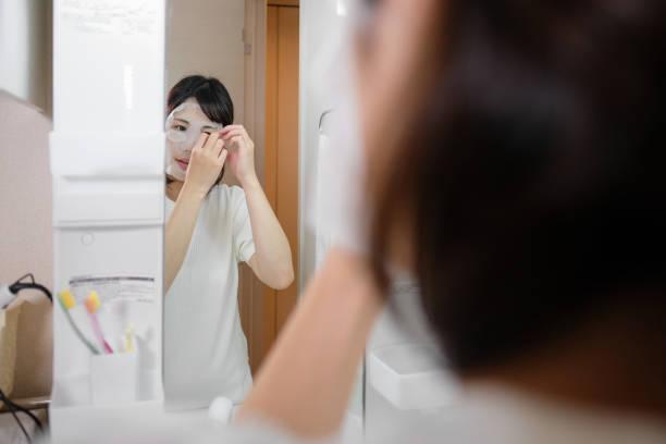 jonge vrouw zetten op gezicht pack - mirror mask stockfoto's en -beelden