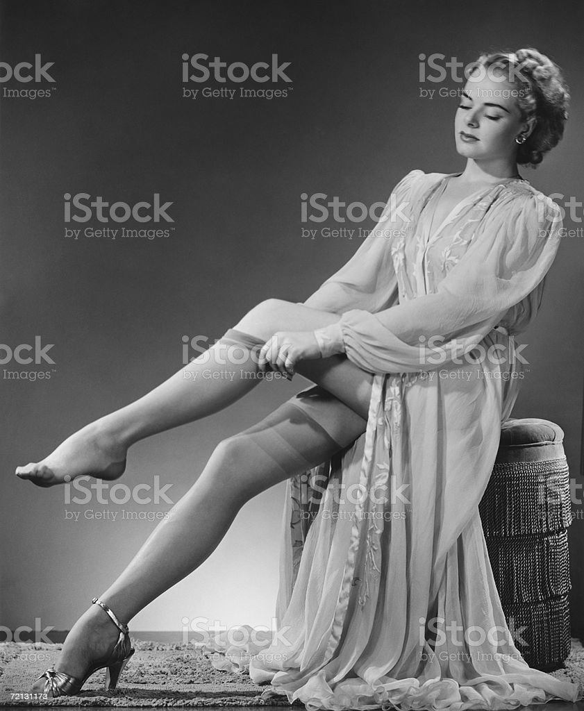 Young woman putting on stockings in studio (B&W) stock photo