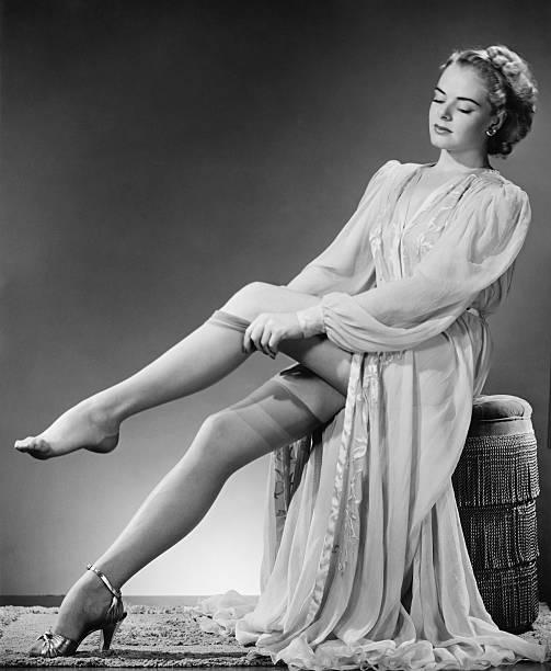 Young woman putting on stockings in studio (B&W) stock photo