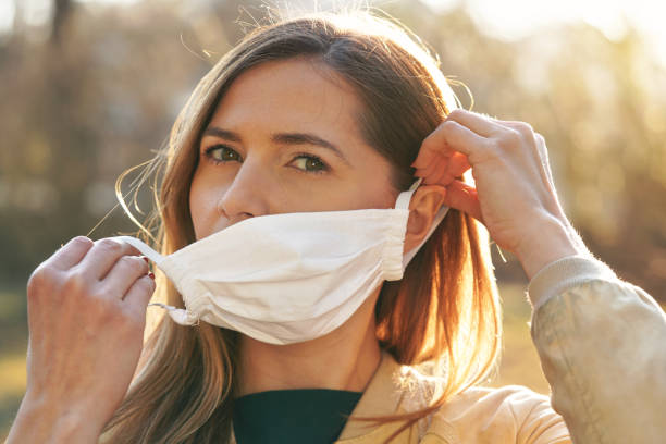 Young woman putting on white cotton home made virus nose mouth face mask, blurred bokeh park in background. Coronavirus covid-19 outbreak prevention stock photo