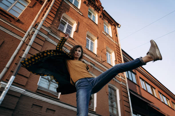 Young woman raises her leg up outdoor in evening stock photo