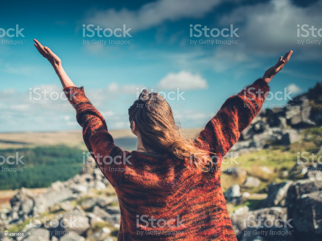 Young woman raising her arms in the wilderness stock photo