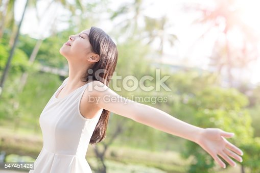 istock young woman raising her arms 547451428