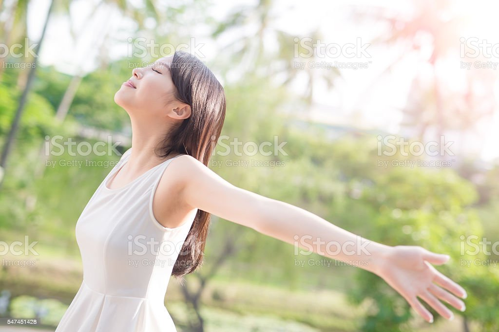 young woman raising her arms stock photo