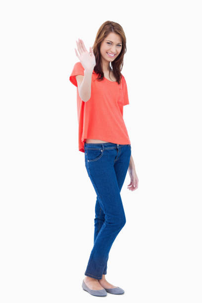 Young woman raising her hand as a greeting stock photo