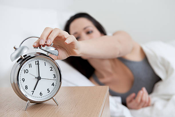 Young woman reaching for alarm clock stock photo