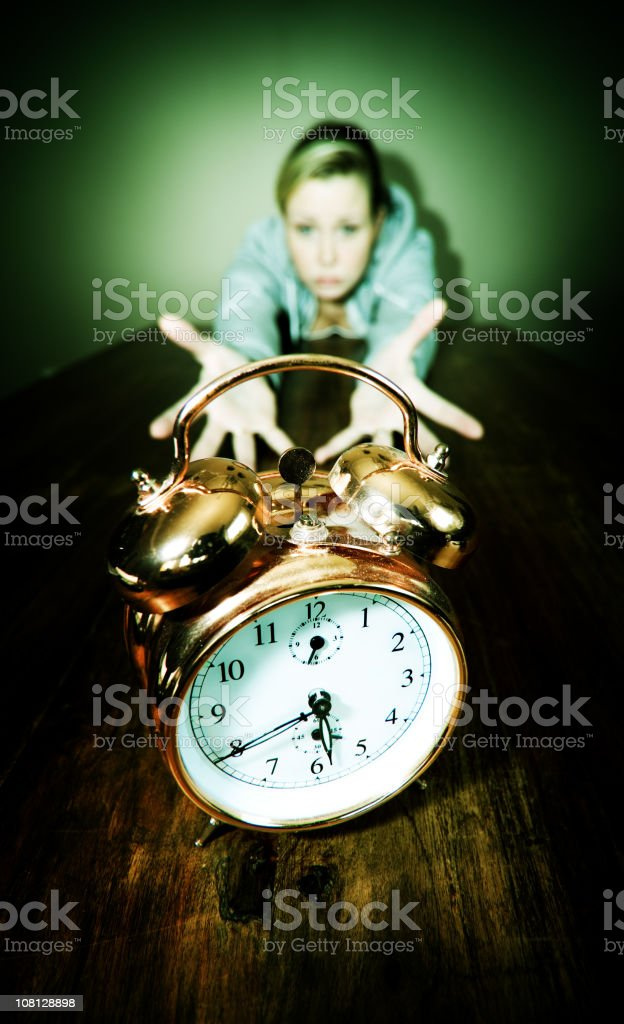 Young Woman Reaching for Clock royalty-free stock photo