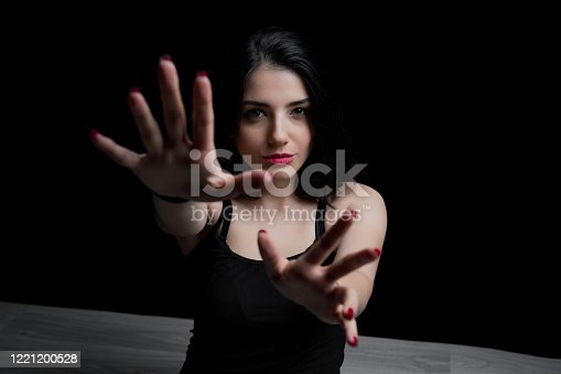 Young woman reaching out with her hand to camera. Portrait of woman on black background