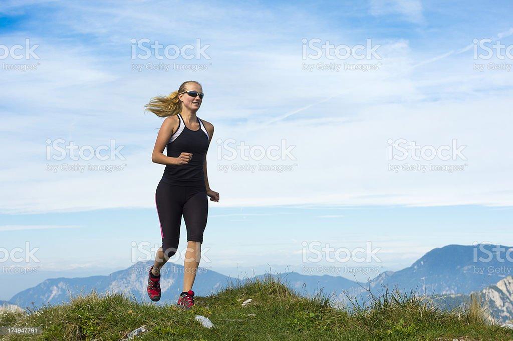Young woman reaching the mountain peak stock photo
