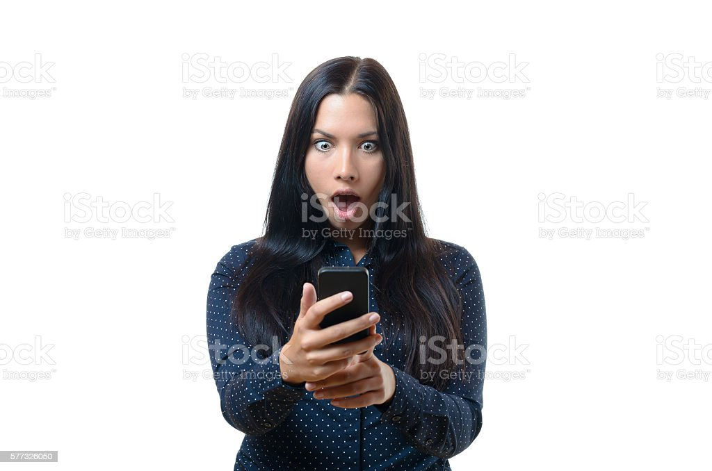 Young woman reacting in horror to her mobile stock photo