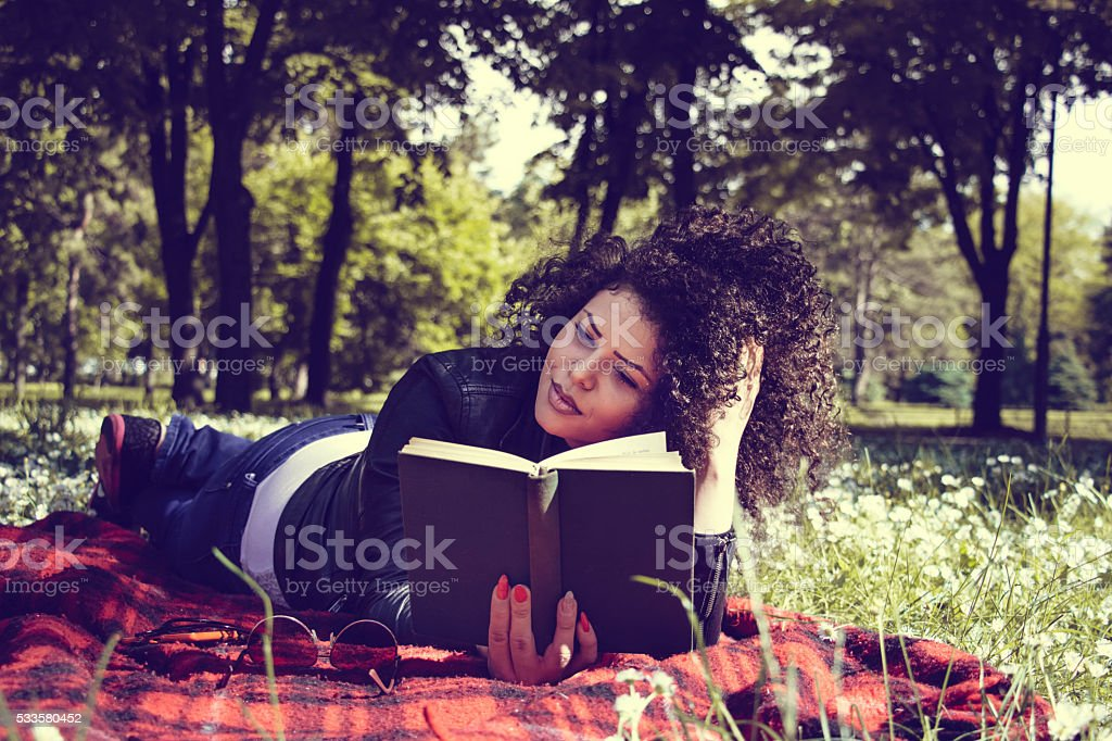 young woman read a book in park on blanket stock photo