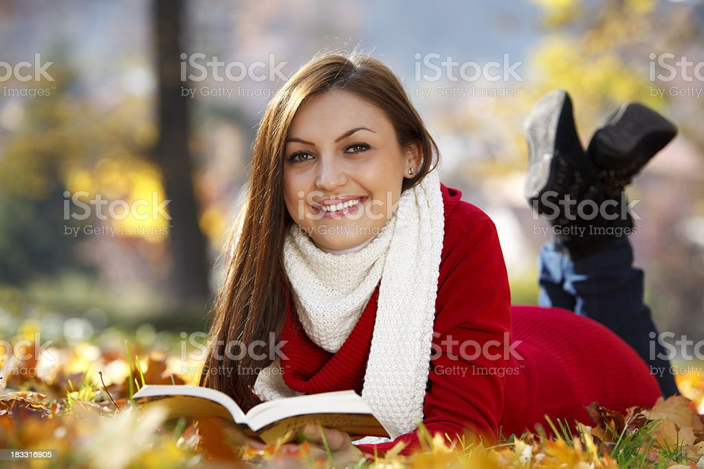 Young woman reading a book and enjoying autumn royalty-free stock photo