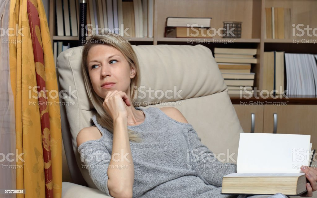 Young woman reading a book at home library, sitting in comfortable armchair photo libre de droits