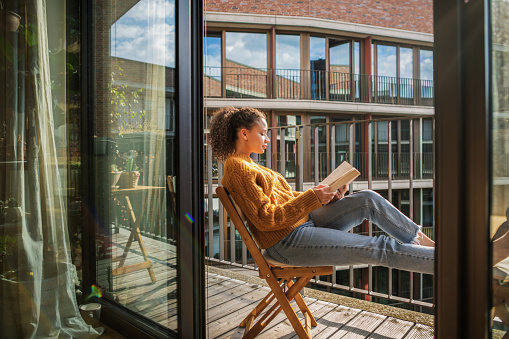 Young girl reads a book on the terrace with a view , feeling relaxed and content