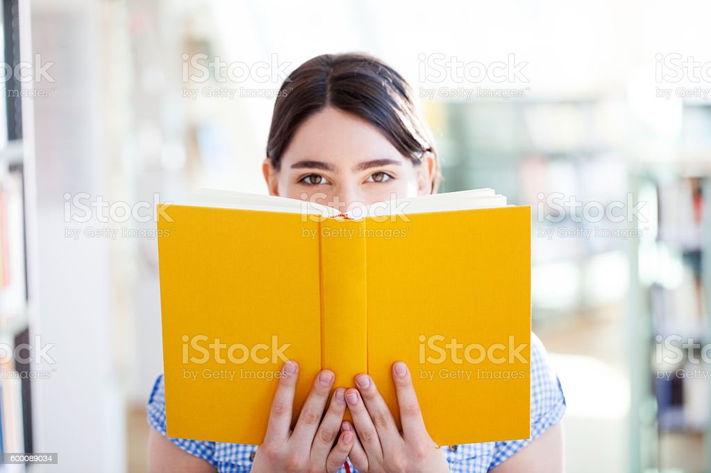 Young woman reading a book at the library