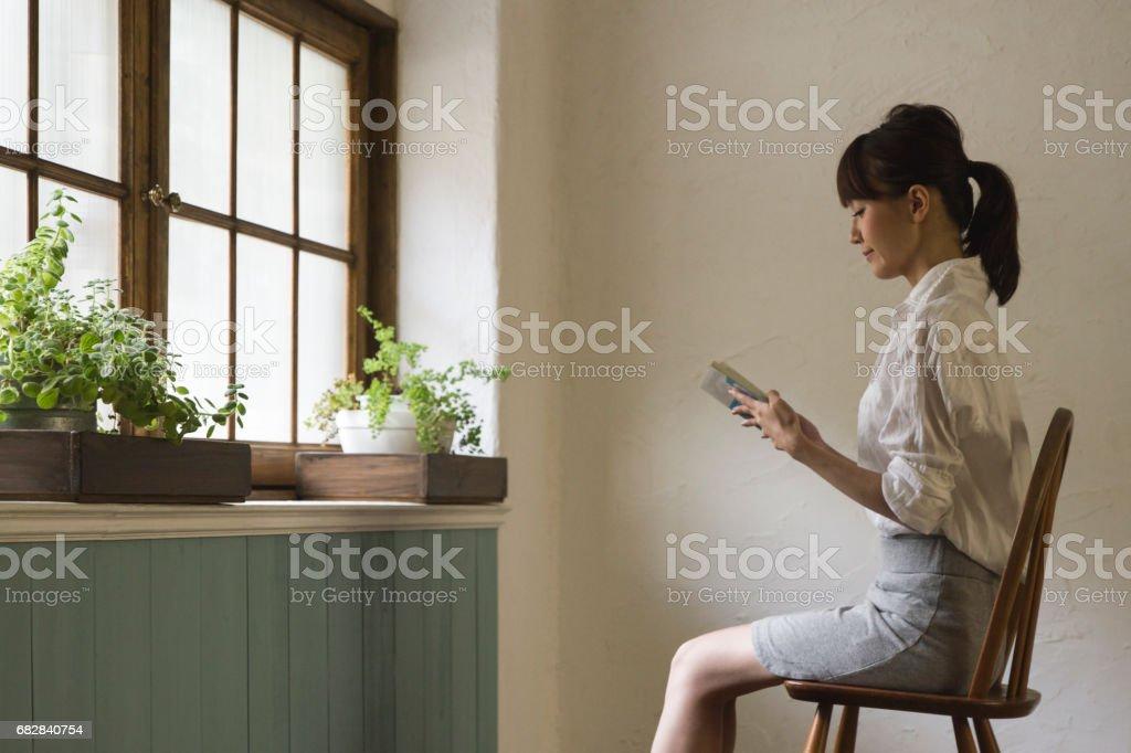 Junge Frau, ein Buch durch das Fenster in einem Raum Lizenzfreies stock-foto