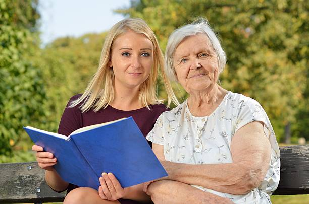 Young woman reading a book elderly woman in the park. stock photo