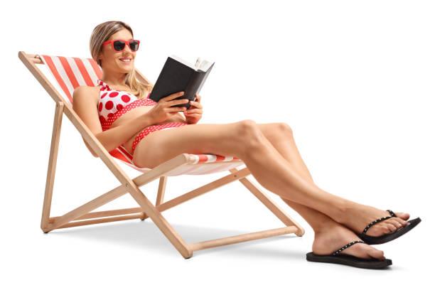 junge frau, die ein buch im liegestuhl lesen - sun chair stock-fotos und bilder
