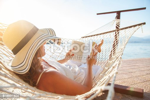 istock Young woman, reading a book in a hammock at sunset. 818507804